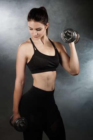 Active young sporty hispanic woman workout with dumbbells isolateda