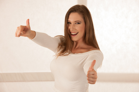 attractive young woman gesture success with thumbs up