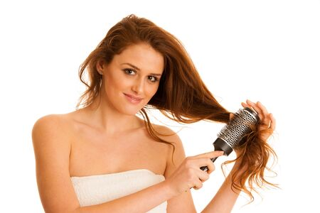 Beautiful young woman combs her hair with a brush isolated over white background