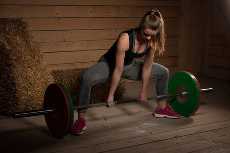 active Woman athlete working out with barbell - powerlifting Stock Photo