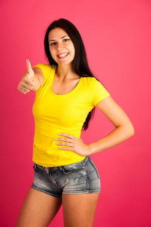 Attractive young woman in yellow t shirt over pink background - teenagers portrait Stock Photo