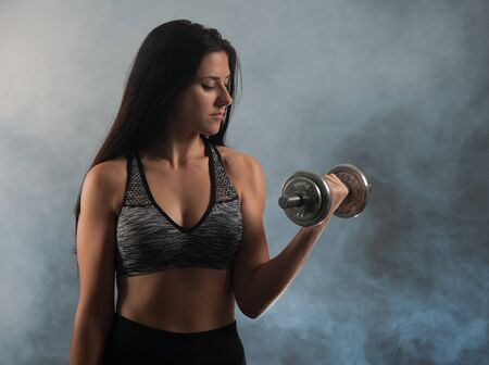 Active young woman workout with dumbbells Stock Photo
