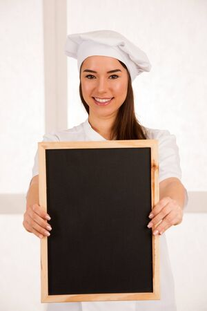 young blonde chef woamn holds kitchenware as she prepares to cook a meal isolated over white background Stock Photo