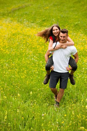 active Playful coupel hiking on a meadow in ratly spring green grass field