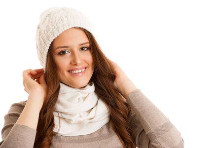 Beautiful young woman in sweater, hat and scarf gestures cold temperatures Stock Photo