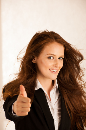 attractive succesful business woman shows tumb up as a gesture for success