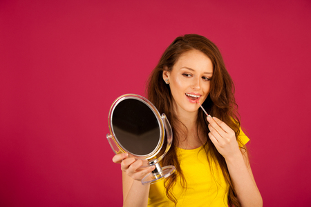 attractive young woman applying lip gloss looking in mirror over pink background Stock Photo