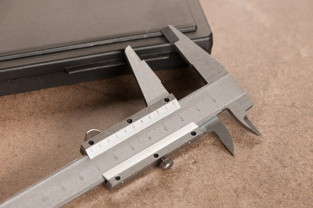 sliding scale: Image of iron calipers close-up on stone desk  background