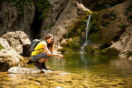 暖かい春の日に山の小川から水を飲むアクティブな若い女性 写真素材