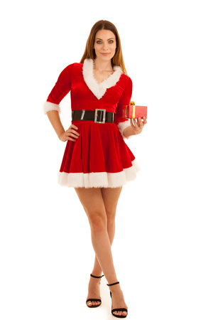 Beautiful young woman in santa claus dress hods a present isolated  over white background