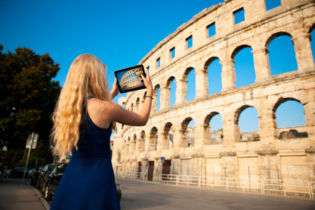 beautiful young woman turist taking photos of Colosseum