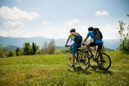 ACTIVO Casal jovem de bicicleta em uma estrada da floresta na montanha em um dia de primavera Foto de archivo - 92623313