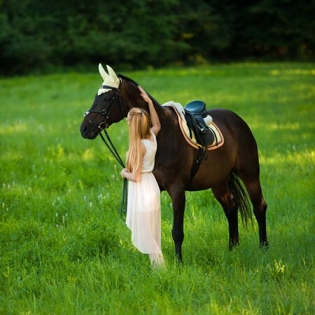 Beautiful young woman with horse outdoor on a walk in nature