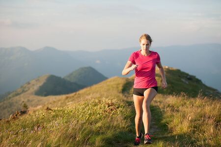 Woman runs on a top of the mountains with mountain range in background Zdjęcie Seryjne