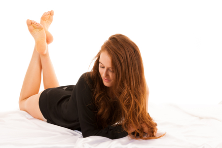 Beautiful young woman with long legs lying on satin sheets in bed