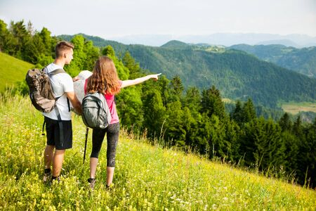 active Beautiful young couple hiking in  nature climbing hill or mountain - man and woman trekking