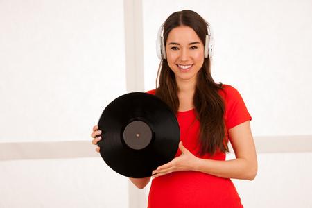 Mooie jonge vrouw in zwarte en gele levendige jurk dansen als ze luistert naar de muziek over roze achtergrond