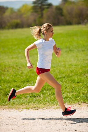 Woman runner runs - workout in spring.