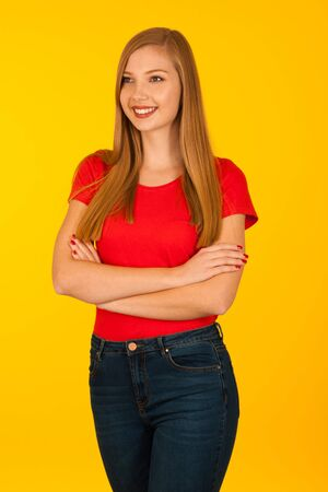 Beautiful young woma in red t shirt and jeans over yellow background