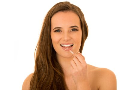 Beautiful young caucasian brunette woman applying lip gloss on her lips isolated over white background Stock Photo