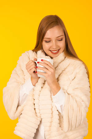 Beautiful woman in a fur winter jacket drinks tea over yellow background - cup of coffee
