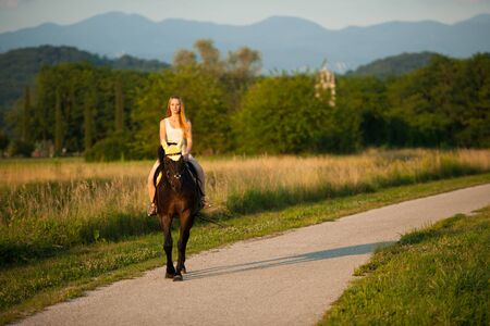 Active young woman ride a horse in nature Stock Photo