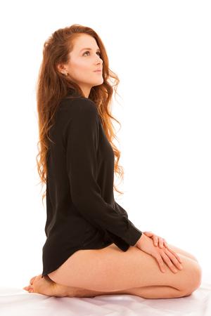 Belle jeune femme brune belle assise sur son lit isolé sur blanc Banque d'images - 97643699