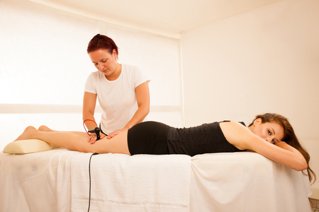 Physiotherapist doing Tecar therapy alterantive treatment on a woman patient