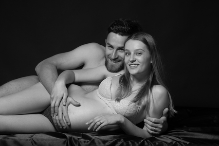 Pregnant woman and her man  studio black and white photography Stock Photo
