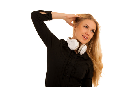 Beautiful young woman listens to the music on headphones and dance isolated over white background