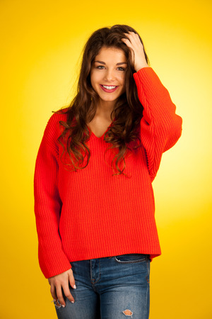 Beautiful young caucasian woman in orange sweater over yellow background - confident teenager Stock Photo