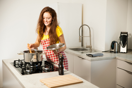 Beautiful young woman cook a meal in the kitchen.