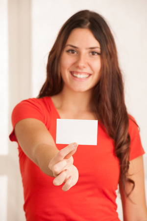Beautiful young woman in red t shirt holds blank card over white background.