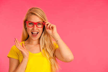 Portrait of a funky young woman in yellow t shirt over pink background