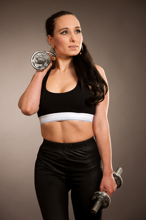 Woman work out arms with dumbbells over gray background .