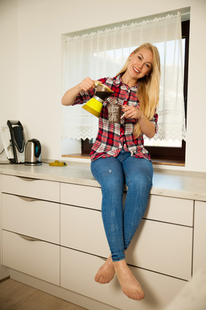 Beautiful young woman cooks coffee in the kitchen.