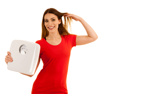 Beautiful young woman holds scale as a sign of weightloss isolated over white background
