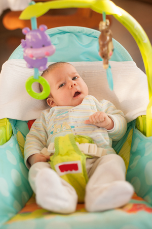Adorable baby boy two months old rests in a chair