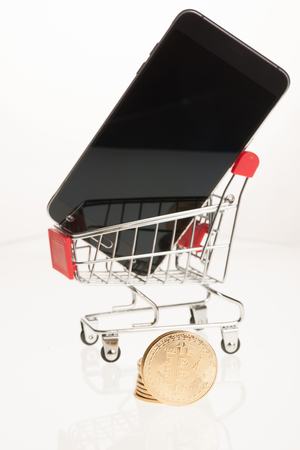 Bitcoin with shopping cart and smartphone isolated over white background