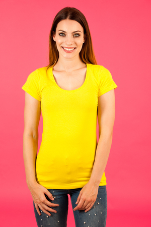 Funky young woman in yellow  t shirt pose over pink background