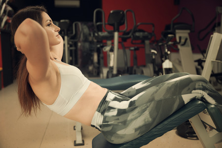 Active young woman working out her abs in fitness club gym Stock Photo