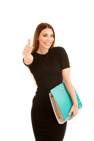 Young business woman in black dress holds a folder shows thumb up sa gesture for success  isolated over white background