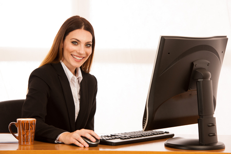 Attractive young business woman works at her desk in the office
