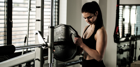 Woman adding weight on a bar as she workout in fitness gym Stock Photo