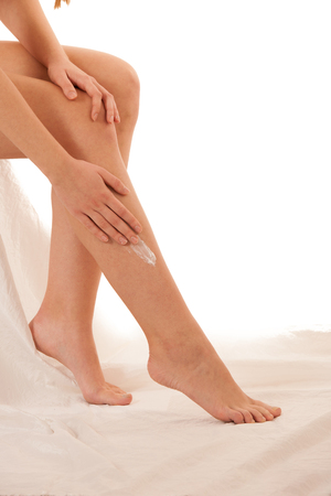 Beautiful elegant young woman applying skin cream on her legs isolated over white Stock Photo