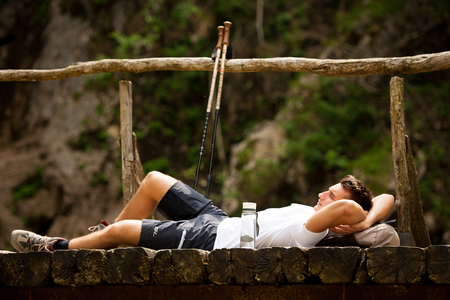 active man resting on a bridge over mountain creek