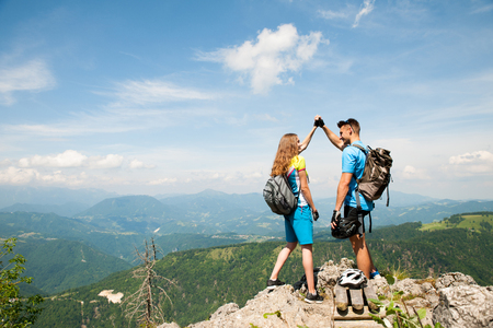 Active couple rests after biking on a mountain top