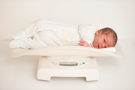 Ten days old new born child on a scale measuring weight
