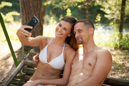 Active young couple taking selfie in park near river Stock Photo