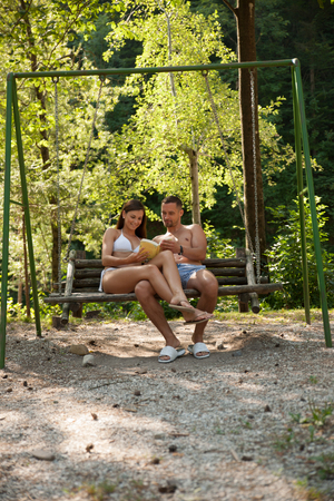 Active young couple reading tourist guide book on a swing in park near river Stock Photo